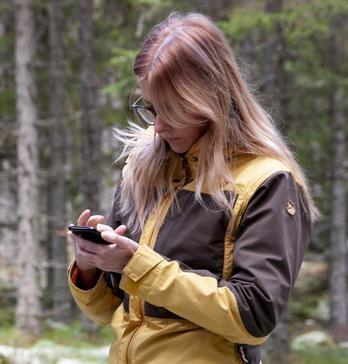 Kvinna med mobil i skog. Foto: Camilla Zilo