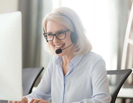 Kvinna med headset vid dator.